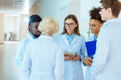 A multiracial group of medical interns in lab coats discussing work. With elder doctor royalty free stock photo