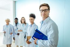 Multiracial group of smiling medical interns in lab coats standing in a row with clipboards royalty free stock image