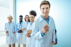Multiracial group of smiling medical interns in lab coats standing in a row with clipboards royalty free stock photography
