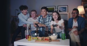 Multiracial group of students having fun with video game in dark apartment. Multiracial group of students are having fun with video game in dark apartment stock footage