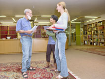 Multiracial group of friendly people chatting in library stock photography