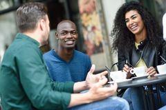 Multiracial group of three friends having a coffee together. A women and two men at cafe, talking, laughing and enjoying their time. Lifestyle and friendship stock photo