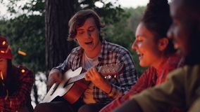 Multiracial group of tourists is having fun in forest playing the guitar and singing songs around campfire in wood near stock footage
