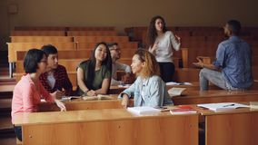 Multiracial group of students are relaxing and chatting during break enjoying free time and communication. Wooden tables. Multiracial group of university stock video footage