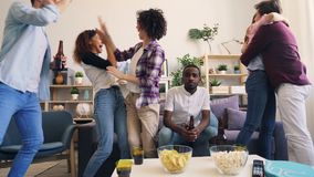 Multiracial group watching football match on TV then hugging doing high-five