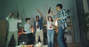 Multiracial group of young people dancing clanging bottles at home party. Multiracial group of young people is dancing clanging bottles having fun at home party stock footage