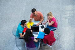 Multiracial group of young students studying together. High angle shot of young people sitting at the table. Stock Photos