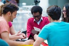 Multiracial grupa młodzi ucznie studiuje wpólnie Wysoki kąta strzał młodzi ludzie siedzi przy stołem zdjęcia stock