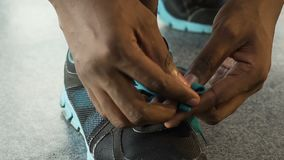 Multiracial guy tying up shoelaces and leaving, basketball player, close-up. Stock footage stock video footage
