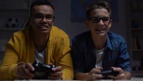 Multiracial guys winning computer game in darkness, risk of losing eyesight