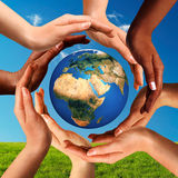 Multiracial Hands Together Around World Globe. Conceptual peace and cultural diversity symbol of multiracial hands making a circle together around the world the royalty free stock image