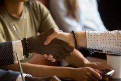 Multiracial handshake greeting during business meeting in cafe Royalty Free Stock Image