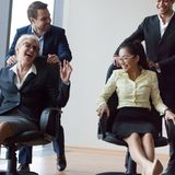 Businesspeople having fun riding on chairs and laughing in offic Royalty Free Stock Image