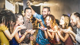 Multiracial happy friend having fun at new year`s eve celebration. Young people blowing confetti at after party in night club stock photo
