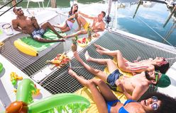 Multiracial happy friends having relax fun at sail boat party - Friendship concept with multi racial people on catamaran sailboat stock images