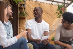 Multiracial happy friends laughing joking studying together with notebooks outdoor stock images