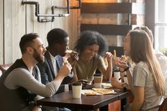 Multiracial happy young people laughing eating pizza together in. Multiracial happy young people eating pizza in pizzeria, black and white cheerful mates Stock Photos