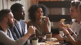 Multiracial happy young people eating pizza at meeting in pizzeria