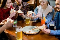 Multiracial happy young people eating pizza in pizzeria, cheerful friends laughing enjoying meal having fun sitting royalty free stock photography