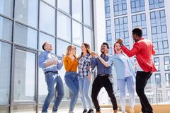 Group of multi ethnic youngsters chilling in urban outdoor background. Multiracial heterosexual group of students having fun on roof party dancing and listening Royalty Free Stock Image