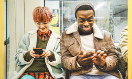Multiracial hipster friends couple having fun with phone. Multiracial hipster friends couple having fun with smartphone in subway train - Urban relationship Royalty Free Stock Photos