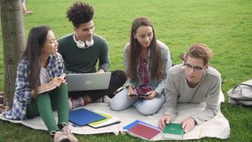 Multiracial hispanic team in discussion using computer along academy campus in summer. Four person talking together, smiling, holding laptop, writing. Mixed stock footage