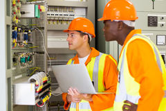 Multiracial industrial technicians. Experienced multiracial industrial technicians checking transformer Royalty Free Stock Photography