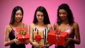 Multiracial ladies in pajamas embracing gifts wondering whats in, temptation