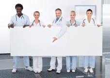Multiracial lekarki trzyma plakat Obrazy Royalty Free