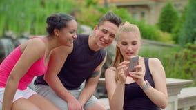 Multiracial ludzie ma zabawę używać telefon w parku Młody przyjaciół śmiać się zbiory wideo