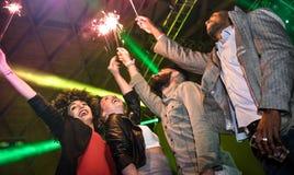 Multiracial młodzi przyjaciele tanczy przy noc klubem z sparkler fi zdjęcie stock