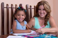 Multiracial mała dziewczyna i jej macierzysty rysunek z kolorów ołówkami Fotografia Stock