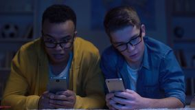 Multiracial male friends surfing net late at night, gadget addiction, eyesight. Stock footage stock video