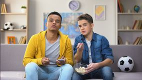 Multiracial male teen friends discussing football match eating popcorn, leisure. Stock footage stock footage