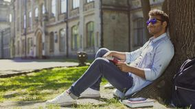 Multiracial man sitting under tree wearing sunglasses, positive mood, energy Stock Image