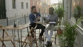 Multiracial men with digital devices talking in outdoor cafe stock video footage