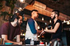 Multiracial men meeting their friend in lounge bar. Real emotions of best friends happy to see each other. Multiracial young men meeting their friend in lounge Royalty Free Stock Photos