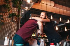 Multiracial men meeting their friend in lounge cafe. Real emotions of best friends happy to see each other. Arabian young men meeting their friend in lounge Stock Photo
