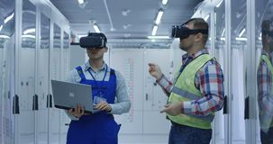 Multiracial men in VR glasses working on electrical station. Adult diverse men standing with laptop and in VR headsets working in control center of solar stock video