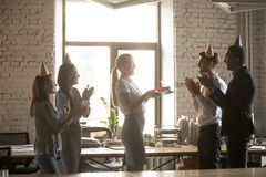 Diverse colleagues congratulate coworker with birthday in office royalty free stock photos