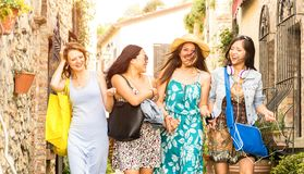Multiracial millennial girlfriends walking and talking in old town tour - Happy girls having fun around city streets stock photos