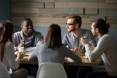Multiracial millennial przyjaciele opowiada pijący kawę wpólnie obrazy royalty free