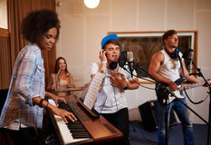 Multiracial music band performing in a recording studio Stock Image