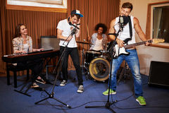 Multiracial music band performing in a recording studio.  Stock Images