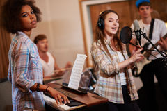 Multiracial music band performing in a recording studio Royalty Free Stock Image