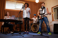 Multiracial music band performing in a recording studio.  Royalty Free Stock Photos