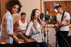 Multiracial music band performing in a recording studio.  Royalty Free Stock Photo