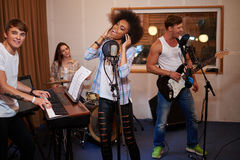 Multiracial music band performing in a recording studio Stock Images