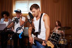 Multiracial music band performing in a recording studio Stock Photo