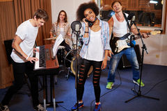 Multiracial music band performing in a recording studio.  Royalty Free Stock Photography